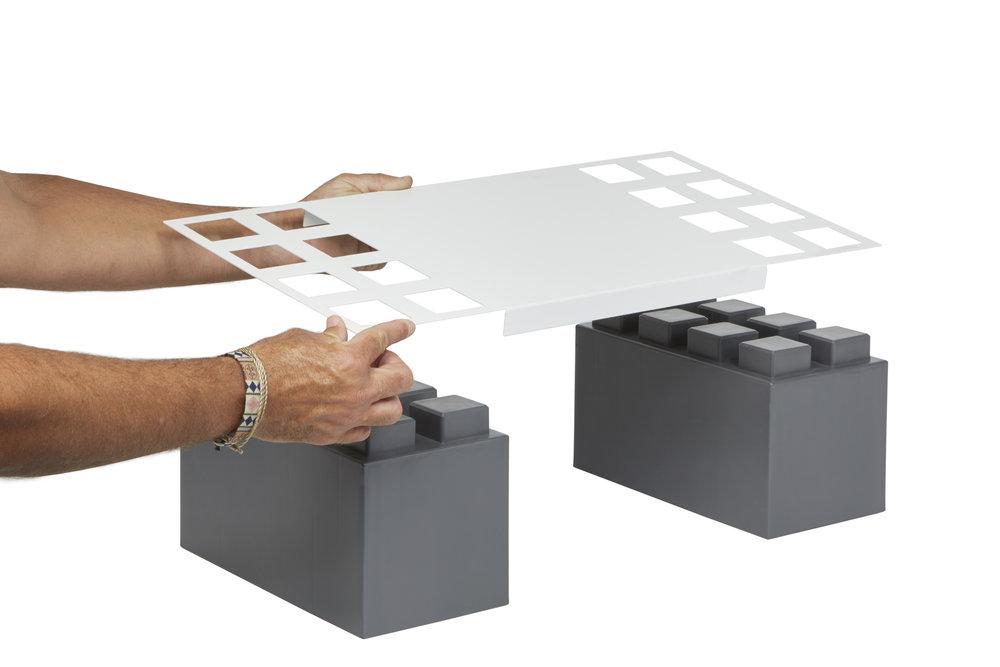2 Hände legen einen Everblock-Regalboden auf 2 dunkelgraue Blöcke