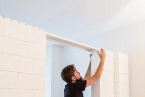 Person legt weißen Everblock Mauersturz auf eine weiße Wand auf