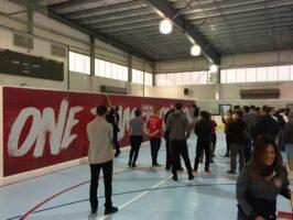 Mit roter Werbung beklebte Eerblock-wand in einer Turnhalle